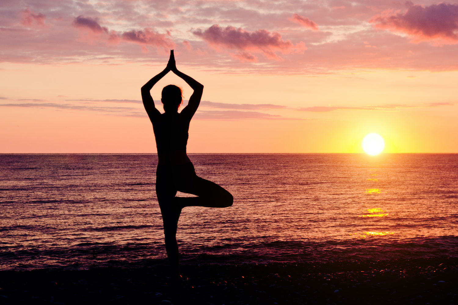 Woman at sunset practicing yoga. Seashore, silhouette